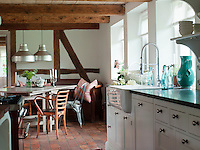 A turquoise vase and bottles cast their colour over the kitchen work surface
