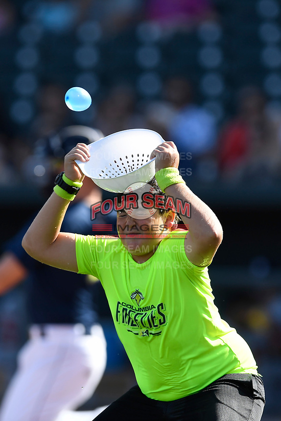 A young fan tries to catch a water balloon using a colander on his head between innings of the South Atlantic League game between the Rome Braves and the Columbia Fireflies on Sunday, July 2, 2017, at Spirit Communications Park in Columbia, South Carolina. Columbia won, 3-2. (Tom Priddy/Four Seam Images)