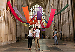 Pictured: A visitor admires the vibrant colours of the art installation 'Held in a Burst of Colour' by Rev'd Gill Sakakini as it drapes across the empty nave at Winchester Cathedral, Hants.<br /> <br /> The bright, bold colours of the fabric pay tribute to the rainbows that people across the country have been placing in their windows during the coronavirus pandemic as a symbol of hope, and welcomes visitors as they enter the Cathedral as it reopened for public service last weekend. <br /> <br /> © Jordan Pettitt/Solent News & Photo Agency<br /> UK +44 (0) 2380 458800