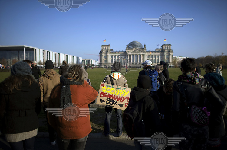 A protestor, outside the Reichstag, holds up a placard that reads: One Love Occupy Germany 99%, during a march linked to the Occupy Movement, a worldwide protest against the banking industry and the prevailing economic system.