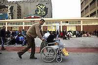 Pictured: A man with a disabled relative with hundreds of other migrants rest on the ground after disembarking at the port of Piraeus Friday 26 February 2016<br /> Re: Hundreds of refugees that crossed the border from Turkey to the Greek islands, have arrived at the port of Piraeus near Athens, Greece