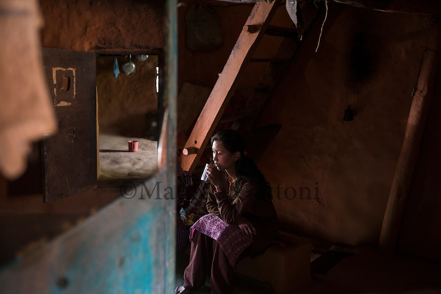 """Nepal - Kathmandu - Sunita Lama, 24, drinks a cup of tea while sitting in her house in the outskirts of the capital. Sunita's husband, Sir Kumar Lama, 30, has just come back from Qatar, where he spent one year working as a welder in a factory. Rather than the promised around 360 USD per month, Lama was paid only 220 USD. Lama decided to come back to Nepal one year prior of the termination of its contract but is now struggling to repay the 1,200-USD-loan he had taken with his brother in order to go to Qatar. """"Most of my co-workers had been cheated as well"""" he explains. """"Some have been working for eight years now, but are still stuck in Qatar because of their debts""""."""