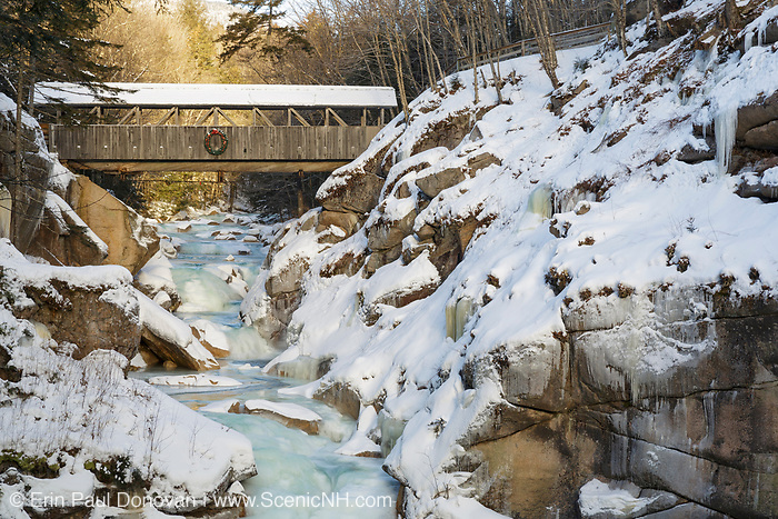 Sentinel Pine Covered Bridge in Franconia Notch of Lincoln, New Hampshire during the winter months. The Sentinel bridge is a footbridge that crosses over the Pemigewasset River.
