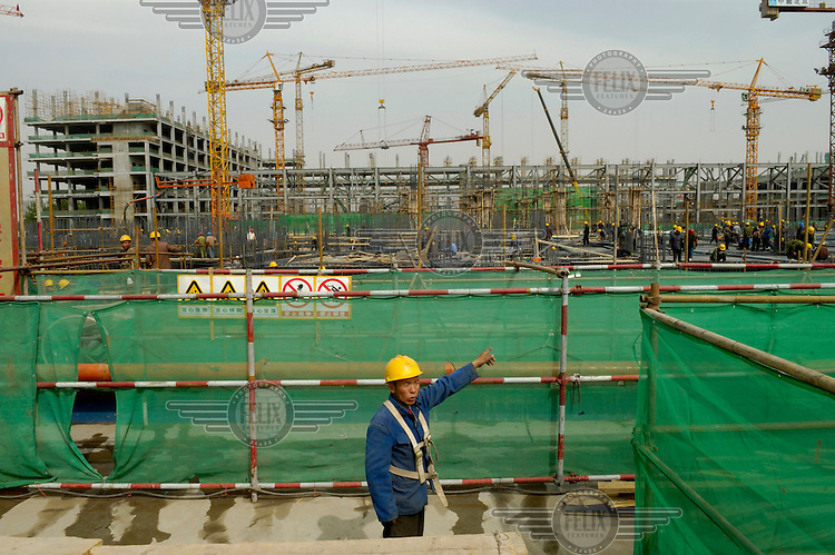 Migrant labourer at work on the construction site of the 2008 Olympic stadium. The original 'bird's nest' design by architects Herzog & de Meuron was simplified by the Chinese once the bid for the Olympic games was successful.
