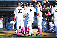 Evan Stephens (5) of the Wake Forest Demon Deacons is congratulated by his teammates after scoring a run against the Duke Blue Devils at Wake Forest Baseball Park on April 25, 2014 in Winston-Salem, North Carolina.  The Blue Devils defeated the Demon Deacons 5-2.  (Brian Westerholt/Four Seam Images)