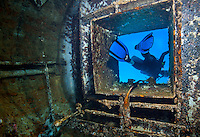 Female scuba diver exits hatch of El Águila wreck; West End, Roatan, Honduras