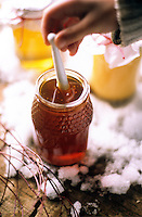 A girl stirs a honey stick in a glass jar filled with golden honey