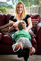 A woman sitting on a sofa breastfeeding her 2 month old baby while playing with her older toddler by bouncing him on her legs.<br /> <br /> Hampshire, England, UK<br /> 10/02/2013