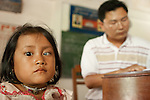 Sing Chum, 7  has an advanced cataract in her left eye.  Dr. Heng Ton is in the background writes her a prescription In Kok Thnot Commune Village School.