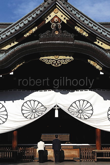 A couple prays at the main hall of Yasukuni Shrine in Tokyo, Japan. very year on August 15, the day Japan officially surrendered in WWII, tens of thousands of Japanese visit the controversial shrine to pay their respects to the 2.46 million war dead enshrined there, the majority of which are soldiers and others killed in WWII and including 14 Class A convicted war criminals, such as Japan's war-time prime minister Hideki Tojo. Each year speculation escalates as to whether the country's political leaders will visit the shrine, the last to do so being Junichiro Koizumi in 2005. Nationalism in Japan is reportedly on the rise, while sentiment against the nation by countries that suffered from Japan's wartime brutality, such as China, has been further aggravated by Japan's insistence on glossing over its wartime atrocities in school text books...Photographer:Robert Gilhooly....Photographer:Robert Gilhooly