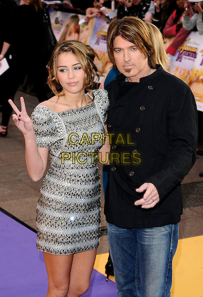"MILEY CYRUS & BILLY RAY CYRUS.UK Premiere of ""Hannah Montana: The Movie"" at the Odeon Leicester Square, London, England..April 23rd 2009 .half 3/4 length silver grey gray beaded beads embellished jewel encrusted dress shoulder pads structured shoulders sculpted bracelets bangles jeans denim black jacket father dad daughter family hand v peace sign .CAP/CAN.©Can Nguyen/Capital Pictures."