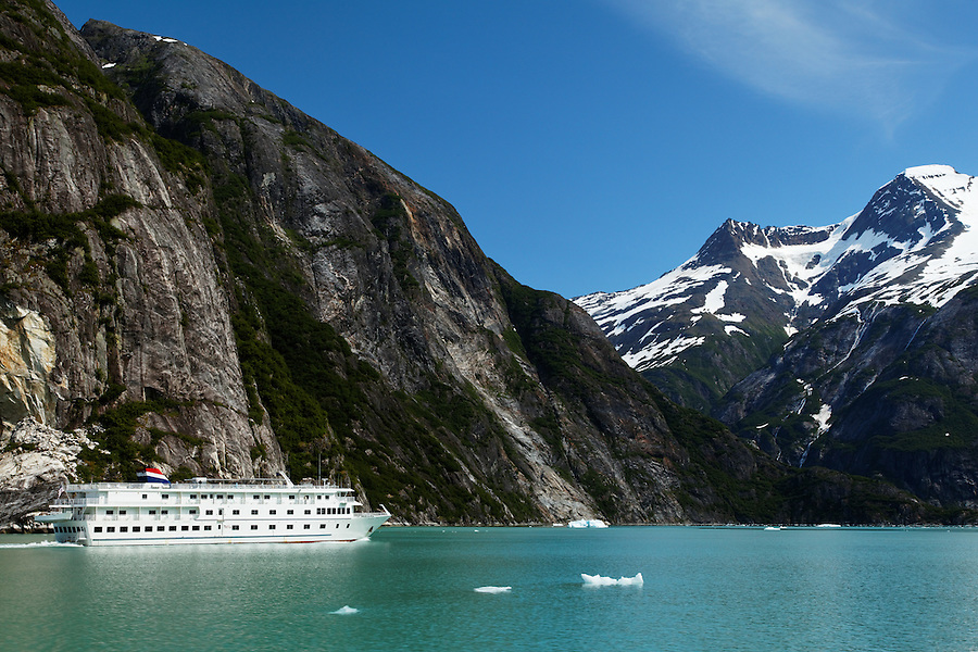 Sheer-walled mountains rise above a small cruise ship on Tracy Arm, Southeast Alaska, USA
