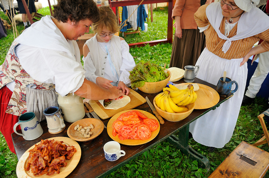 Families often accompanied soldiers on campaigns to feed and nurse the troops, at a Revolutionary War encampment, Old Sturbridge Village, Massachusetts, USA.