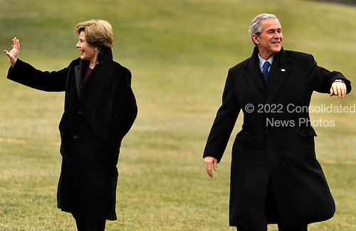 Washington, DC - January 18, 2009 -- United States President George W. Bush (R) and first lady Laura Bush wave as they return to the White House in Washington from a weekend at the presidential retreat at Camp David, 18 January 2009.  Bush, on his last sheduled flight on Marine One, returned to a frigid Washington, that despite the temperatures, is caught up in a swirl of inauguration activities for President-elect Barack Obama on 20 January.   .Credit: Mike Theiler - Pool via CNP
