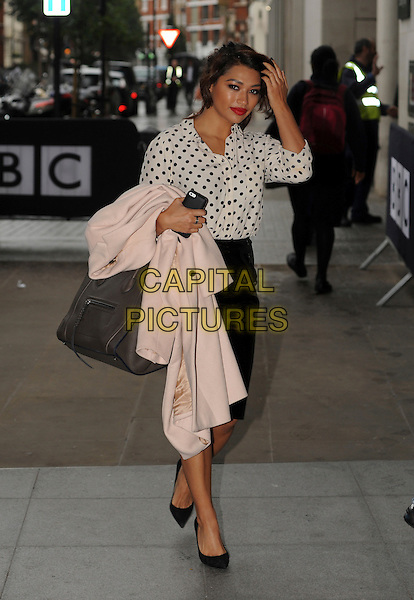 The Saturdays - Vanessa White  <br /> At BBC Radio 1, London, England.<br /> October 22nd, 2013<br /> full length black white polka dot blouse leather skirt carrying holding pink coat jacket <br /> CAP/AOU<br /> &copy;AOU/Capital Pictures