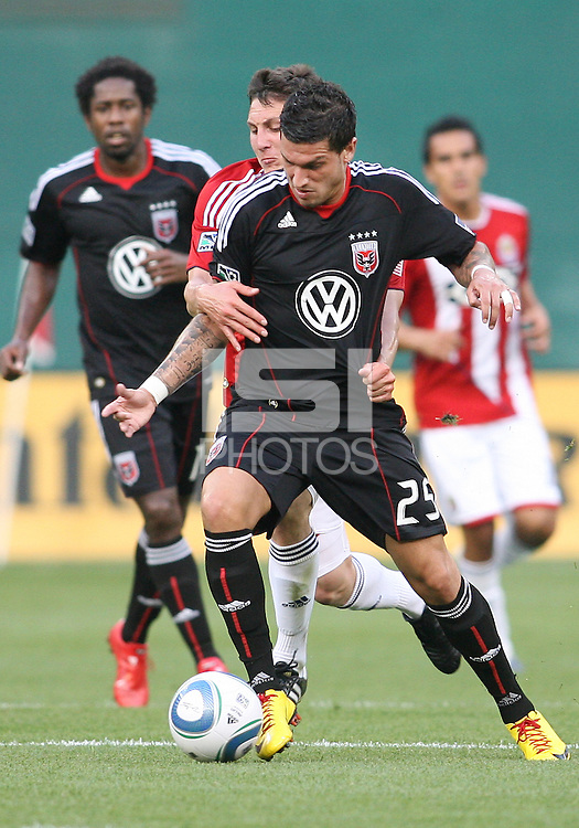 Santino Quaranta #25 of D.C. United is held back by Ben Zemanski #21 of Chivas USA during an MLS match at RFK Stadium, on May 29 2010 in Washington DC. United won 3-2.