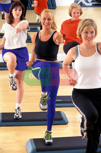 young women enjoying step exercise workout in health club studio