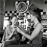 Two young qwomen drinking in a bar