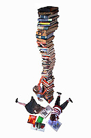 Children reading next to a book tower