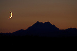 A waxing moon sets over the Olympic Mountains  on Friday, July 24, 2009. In  the northern hemisphere, if the left side of the Moon is dark then the light part is growing, and the Moon is referred to as waxing (moving towards a full moon). If the right side of the Moon is dark then the light part is shrinking, and the Moon is referred to as waning (moving towards a new moon).  ©2012. All RIghts Reserved. Jim Bryant.