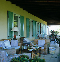Wicker furniture is grouped on a shady paved terrace on the leeward side of the house
