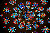 Medieval western rose  window of the Gothic Cathedral of Chartres, France. A UNESCO World Heritage Site. The western rose, made c.1215 and 12 m in diameter shows the Last Judgement - a traditional theme for west façades. A central oculus showing Christ as the Judge is surrounded by an inner ring of 12 paired roundels containing angels and the Elders of the Apocalypse and an outer ring of 12 roundels showing the dead emerging from their tombs and the angels blowing trumpets to summon them to judgement.