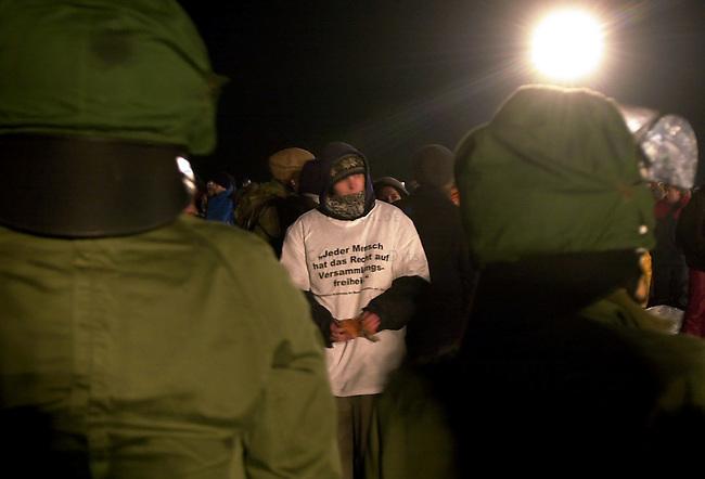 Proteste gegen Castor-Transport<br /> Ein Transport von zwoelf Castoren aus der franzoesichen Wiederaufbereitungsanlage La Hague wurde am Donnerstag den 14. November 2002 per LKW von Dannenberg nach Gorleben gebracht. In der Nacht vor dem Transport versuchten ca. 1.000 Menschen mit einer Strassenblockade einen letzten Versuch den Transport zu stoppen. Sie wurden jedoch von Polizei und Bundesgrenzschutz von der Strasse getragen und auf einem Feld eingekesselt.<br /> Der Transport des Atommuell lief ab morgens um 6.27 Uhr von Dannenberg in das sogenannte Zwischenlager bei Gorleben reibungslos.<br /> Hier: Eingekesselte Demonstranten von mobilen Flutlichtern der Polzei beleuchtet hinter Polizeiketten.<br /> 14.11.2002, Laase / Niedersachsen<br /> Copyright: Christian-Ditsch.de<br /> [Inhaltsveraendernde Manipulation des Fotos nur nach ausdruecklicher Genehmigung des Fotografen. Vereinbarungen ueber Abtretung von Persoenlichkeitsrechten/Model Release der abgebildeten Person/Personen liegen nicht vor. NO MODEL RELEASE! Nur fuer Redaktionelle Zwecke. Don't publish without copyright Christian-Ditsch.de, Veroeffentlichung nur mit Fotografennennung, sowie gegen Honorar, MwSt. und Beleg. Konto: I N G - D i B a, IBAN DE58500105175400192269, BIC INGDDEFFXXX, Kontakt: post@christian-ditsch.de<br /> Bei der Bearbeitung der Dateiinformationen darf die Urheberkennzeichnung in den EXIF- und  IPTC-Daten nicht entfernt werden, diese sind in digitalen Medien nach &sect;95c UrhG rechtlich geschuetzt. Der Urhebervermerk wird gemaess &sect;13 UrhG verlangt.]