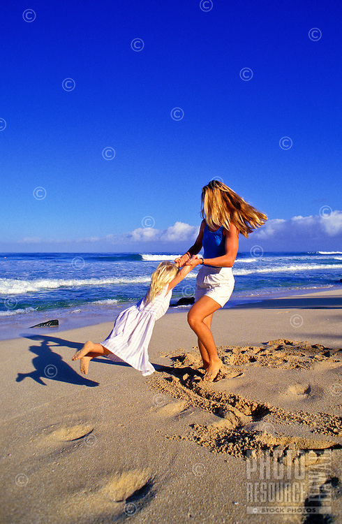 Mother swinging and playing with her daughter on the beach