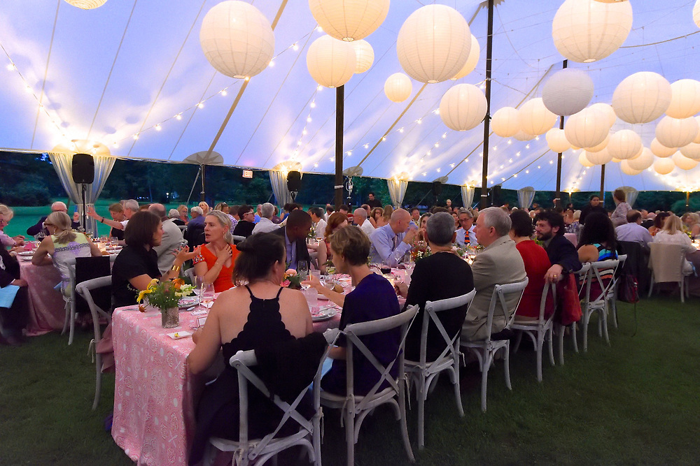 Indoor view of tent with lanterns glowing at a summer gala fundraiser dinner.