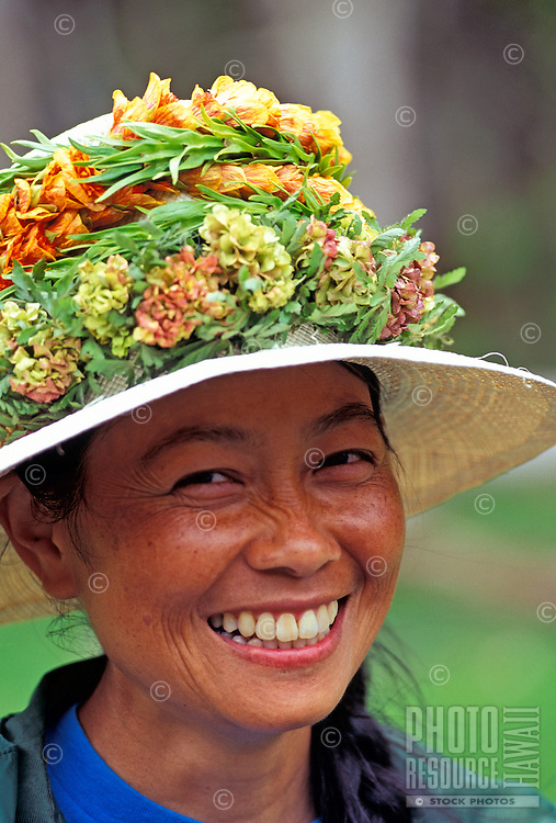 Close-up of a smiling Big Island woman in hat with haku leis.
