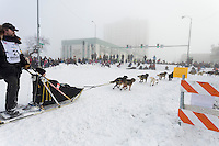 Gerry Willomitzer runs on 4th avenue at Cordova street in the fog as spectaors line the streets during the ceremonial start of the Iditarod sled dog race Anchorage Saturday, March 2, 2013. ..Photo (C) Jeff Schultz/IditarodPhotos.com  Do not reproduce without permission