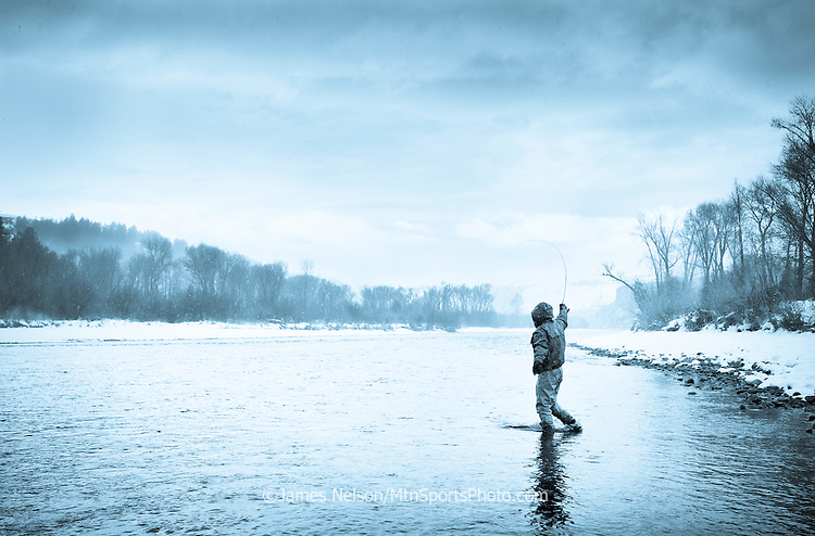 A fly fisherman plays a trout as snow falls at dusk on the South Fork of the Snake River, Idaho.