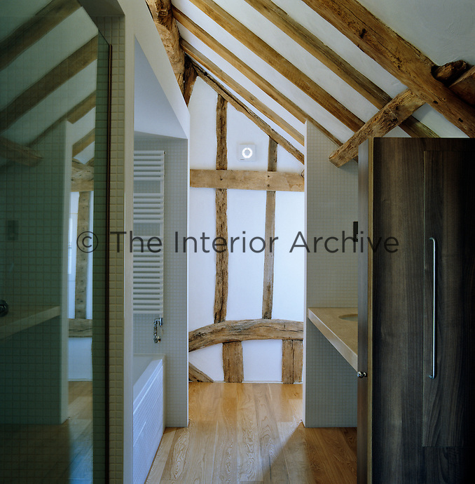 A modern bathroom has been built under the vaulted ceiling and around the exposed beams