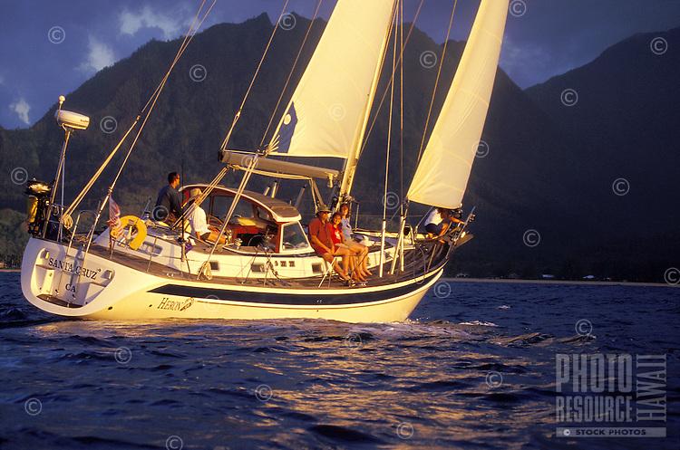 Family sailing a 48 foot yacht at sunset in Hanalei Bay, North Shore of Kauai