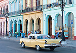 Havana, Cuba; a classic yellow and white 1957 Ford driving down the Paseo de Marti past colorful, pastel buildings