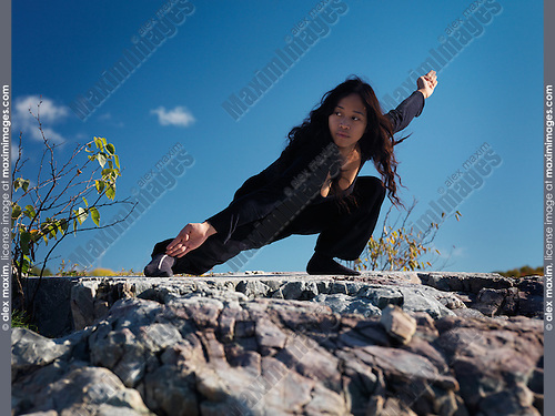 Young asian woman martial artist practicing Kung Fu in the nature under blue sky. Pu Bu stance. Ontario, Canada.