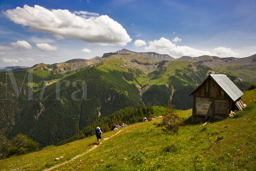 Hiker walks past a shepherd?s hut on the GR5 on Alpine pastures above the Roya Valley. Mont Mounier. Parc National du Mercantour. Alpes-Maritimes. Provence, France.   Model released.
