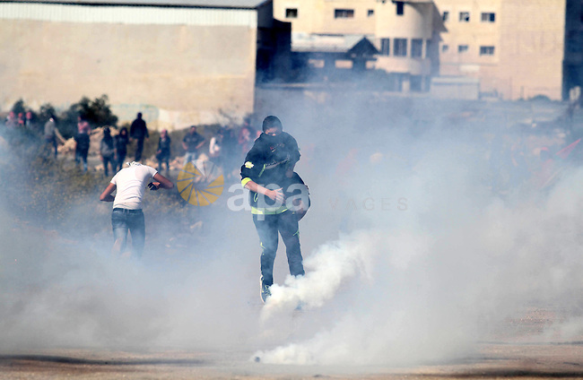 Palestinian protesters run for cover from tear gas fired by Israeli security forces during clashes at a protest to show solidarity with al-Aqsa mosque, outside Israel's Ofer military prison near the West Bank city of Ramallah October 21, 2014. A Palestinian official on Monday called for holding an emergency Arab and Islamic summit to discuss Israeli plans to divide the Al-Aqsa Mosque compound between Jews and Muslims. In recent months, groups of Jewish settlers accompanied by Israeli security forces have repeatedly forced their way into East Jerusalem's flashpoint Al-Aqsa Mosque complex. Photo by Shadi Hatem