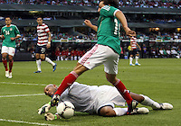 MEXICO CITY, MEXICO - AUGUST 15, 2012:  Tim Howard (1) of the USA MNT dives at the feet of Andres Guardado (MEX) of  Mexico during an international friendly match at Azteca Stadium, in Mexico City, Mexico on August 15. USA won 1-0.