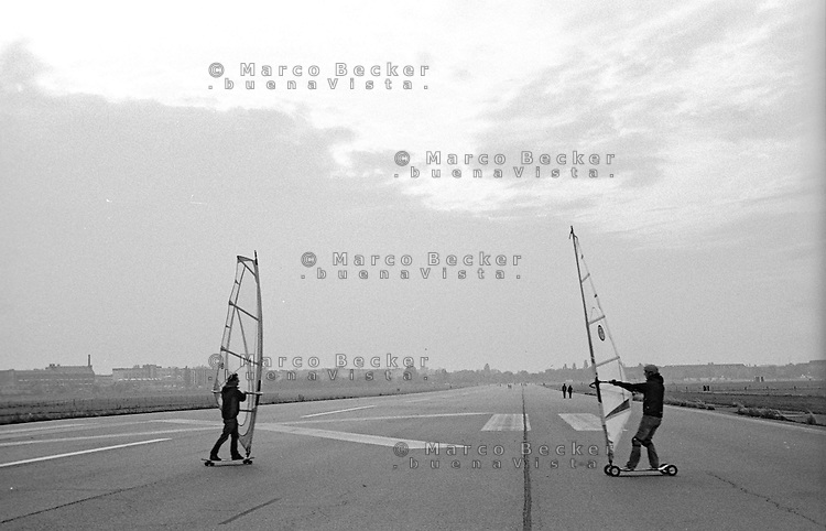 Berlino, aeroporto di Tempelhof riqualificato a parco pubblico. Due ragazzi fanno windskate sulla pista --- Berlin, Tempelhof airport requalified to public park. Two young men sail the runway on windskate