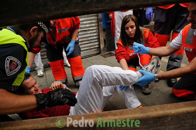 The red Cross workers attend a runner during the fourth run of the bulls of the San Fermin festival, on July 10, 2012, in the northern Spanish city of Pamplona. The festival is a symbol of Spanish culture that attracts thousands of tourists to watch the bull runs despite heavy condemnation from animal rights groups. (c) Pedro ARMESTRE