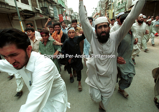 Demonstrators running in the narrow streets after burning a doll of US President George Bush at a pro-Taleban demonstration on September 21, 2001 in the old town in Peshawar, Pakistan. During a national strike people demonstrated all over the country in support of Osama Bin Laden and the Taleban movement in Afghanistan..Photo: Per-Anders Pettersson/ Grazia Neri..