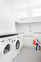 A white utility room with built in cupboard storage and a washing machine and tumble dryer below the worktop.