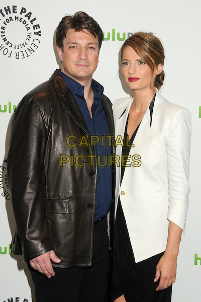 "Nathan Fillion, Stana Katic.PaleyFest 2012 Presents ""Castle"" held at The Saban Theatre, Beverly Hills, California, USA, 9th March 2012..half length leather jacket white blue shirt dress black .CAP/ADM/BP.©Byron Purvis/AdMedia/Capital Pictures."