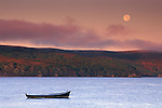 Full moon setting over fog Tomales Bay and lone dory boat at sunrise near Point Reyes Marin California