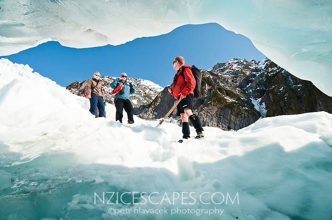Tourists in front of a beautiful ice cave on Franz Josef Glacier - Westland National Park, West Coast, New Zealand