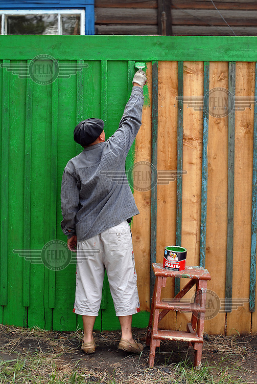 A man paints a fence in the centre of Kyzyl.