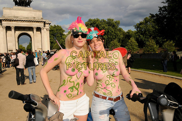 8th London World Naked Bike Ride.Naked bikers taking part in a peaceful protest against oil dependency and car culture ride from Hyde Park around Wellington Arch, Hyde Park Corner.atmosphere general view gv bicycle ride riding skin flashing bodypaint nipple breasts hat.CAP/IA.©Ian Allis/Capital Pictures.