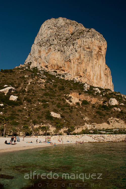 People in the beach at the foot of Peñon de Ifach. Calpe, Alicante province, Costa Blanca, Spain, Europe.