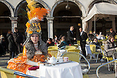 Venice, Italy, 8 February 2015. A woman in costume sits in one of the outdoor restaurants in St Mark's Square. People wear traditional masks and costumes to celebrate the 2015 Carnival in Venice. carnivalpix/Alamy Live News